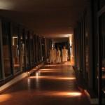 Les frères sortent de l'église en procession, capuchon en tête. La galerie est éclairée d'une lumière tamisée.