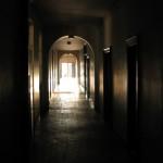 Couloir assombri par l'ombre de la galerie du cloitre et débouchant sur la lumière de la galerie des glaces.