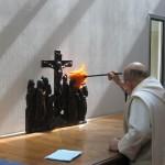 Un frère fait la poussière d'un bas-relief éclairé par un rayon de soleil.