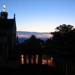 Au loin, face à la vierge du clocher de la grande église, le soleil levant colore le ciel de rose. Le cloître est plongé dans l'obscurité. Seule la galerie qui conduit à l'église est sobrement illuminée.