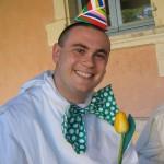 Un jeune frère est revêtu d'un chapeau pointu et d'un grand nœud papillon vert à pois blancs.