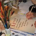 Photo prise par dessus l'épaule d'un frère concentré sur sa feuille de travail, entouré des ses plumes et pinceaux.