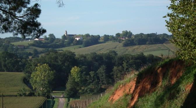 Un talus de terre rouge sur la droite, une petite route en face de nous, un champs de maïs en fleurs plus bas sur la gauche. Le regard est conduit vers l'abbaye perchée sur sa colline, en face.