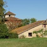 """Dans les jardins de l'abbaye, on peut apercevoir l'alignement du """"petit cazalet"""", une maison landaise traditionnelle, avec l'abside puis le clocher de la Vieille église. Le tout est enveloppé d'une végétation qui commence à prendre ses couleurs d'automne."""