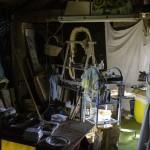 fr Vincent dans son atelier rempli de matériel. La sous-pente du toit laisse peu d'espace.