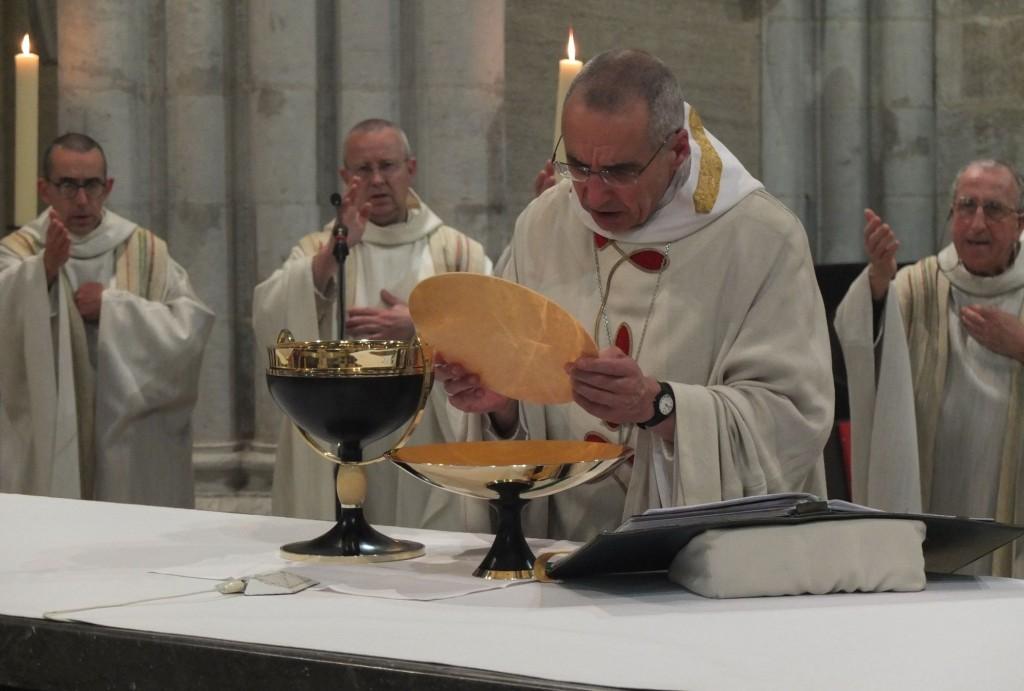 Le père abbé porte dans sa main la grande hostie. Il a devant lui la patène et la coupe de concélébration en or, ébène et ivoire. Par derrière, les concélébrants.