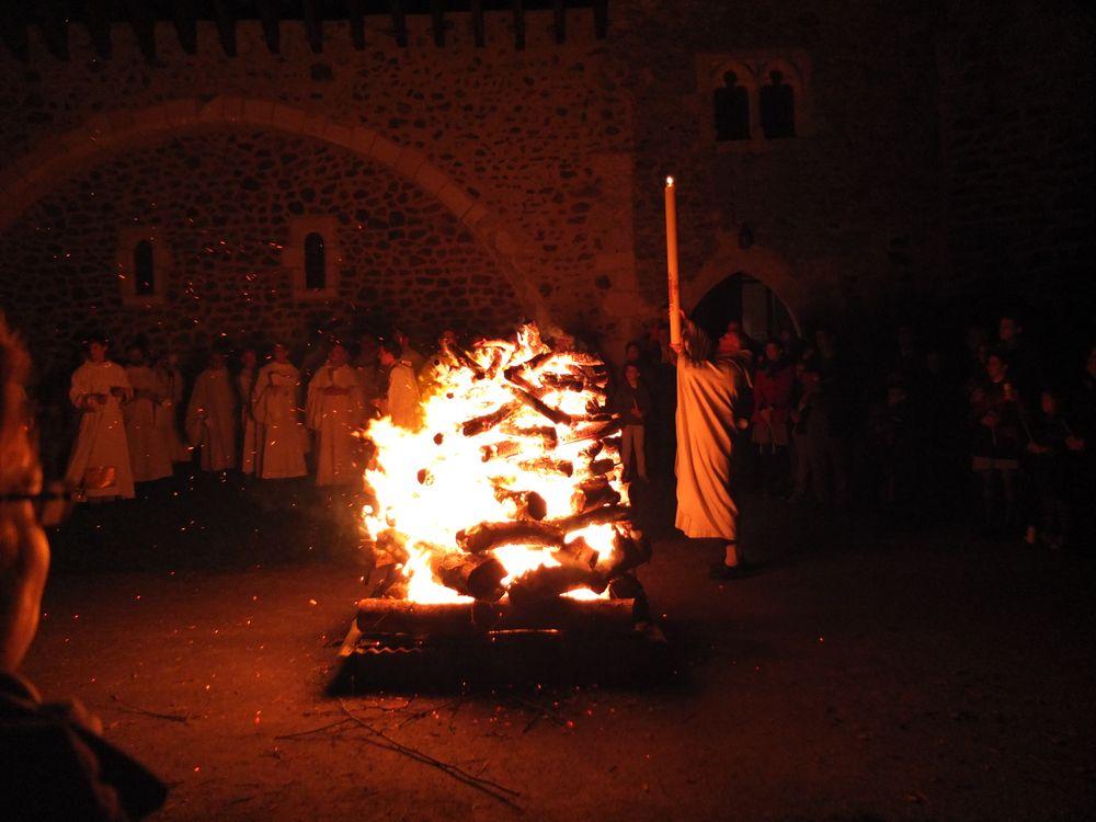Le cérémoniaire, juste devant un grand feu attisé par le vent, élève le cierge pascal qu'il vient d'allumer. Il invite l'assemblée à acclamer le Christ, lumière du monde.