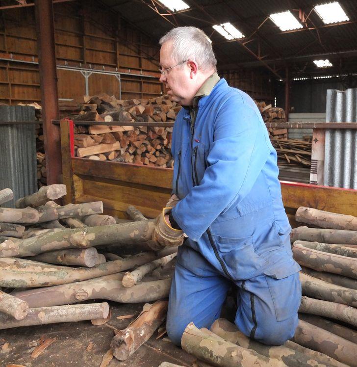 Un frère manipule des billots de bois.