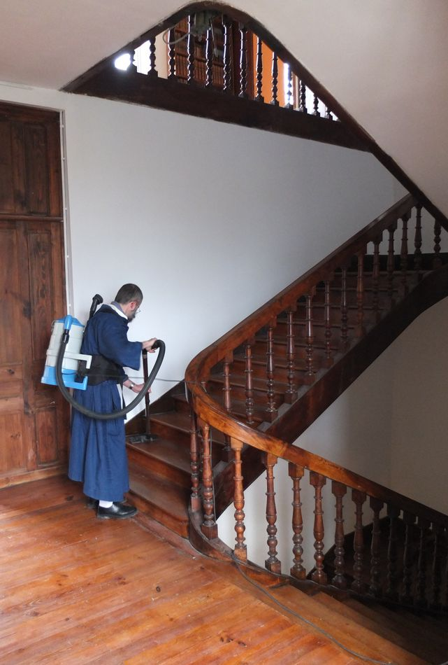 Un frère aspirant la cage d'escalier.