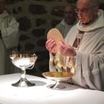 Le père abbé fractionne le Corps du Christ.