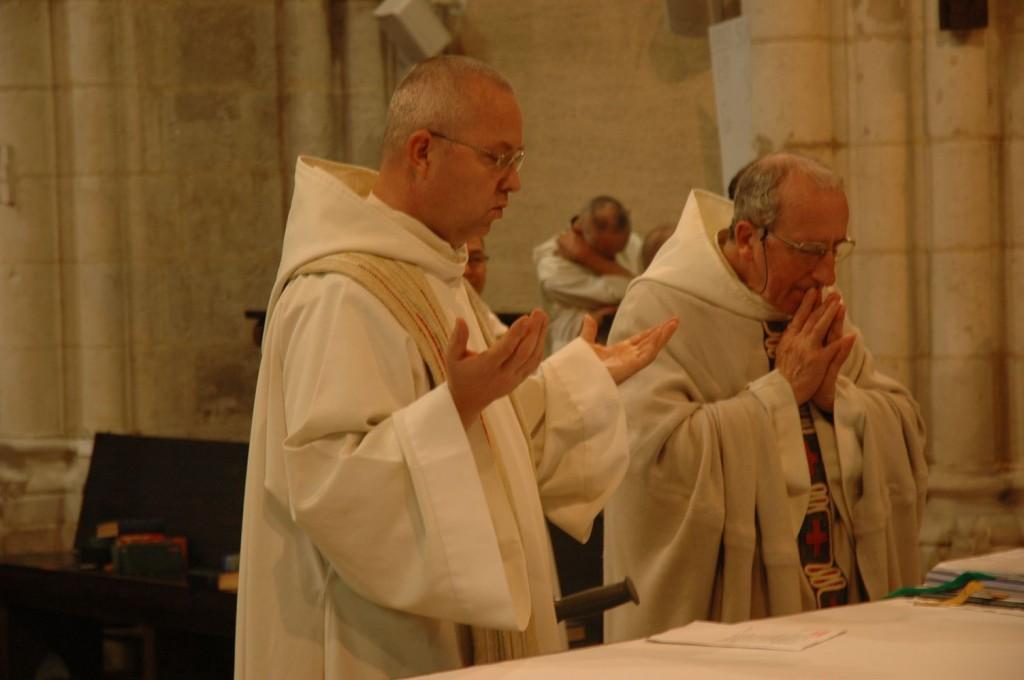 Sur la gauche, un prêtre prie les mains levées, tandis que le célébrant principal se tient les mains jointes sur la droite. Les intercessions pour l'Église et le monde contenues dans la Prière eucharistique sont proclamées par des frères concélébrant.