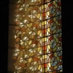 La lumière passe à travers le vitrail dont les couleurs se reflètent sur la profondeur du mur.
