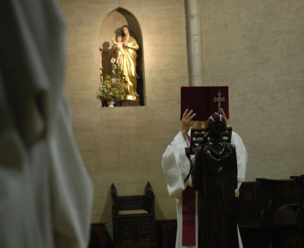 Au milieu, le père abbé vêtu d'une étole violette élève l'évangéliaire pour l'acclamation. La photo nous situe dans le chœur des moines, avec un frère qui apparait sur la gauche.