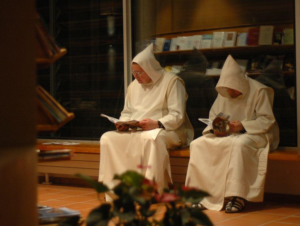Deux moines, capuchons en tête, sont côte à côte et lisent des revues.