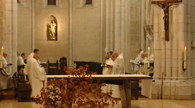 Derrière l'autel, la communauté chante l'office en présence du Christ. Un grand bouquet de feuillages d'automne orne l'autel.