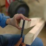 Un frère mesure un bout de bois.
