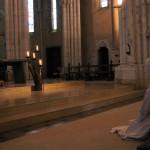 Un frère prie à genoux devant la Croix exposée le Vendredi Saint.