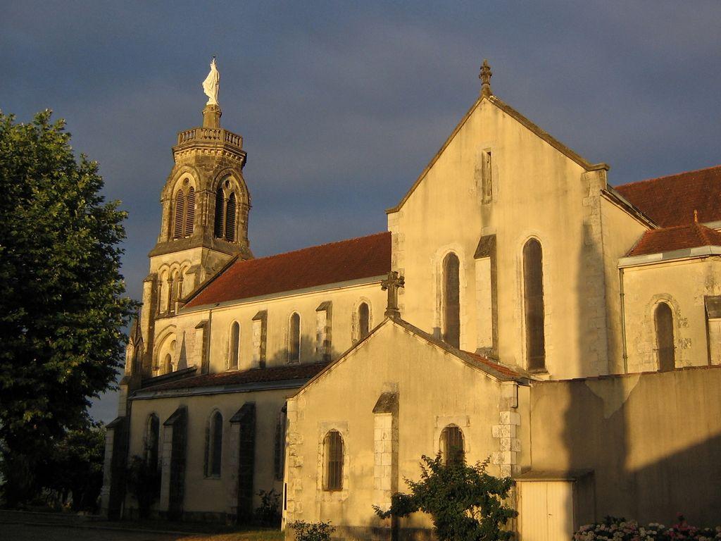 La façade ouest éclairée par le soleil couchant, sur fond de ciel couvert.
