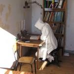 Un frère lisant à sa table de travail, capuchon en tête.