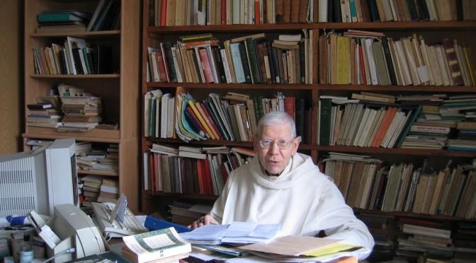 Un vieux moine intellectuel. Derrière lui une bibliothèque, et devant lui un bureau où s'entassent livres et papiers.