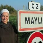 Une soeur en habit brun et voile blanc devant le panneau de Maylis