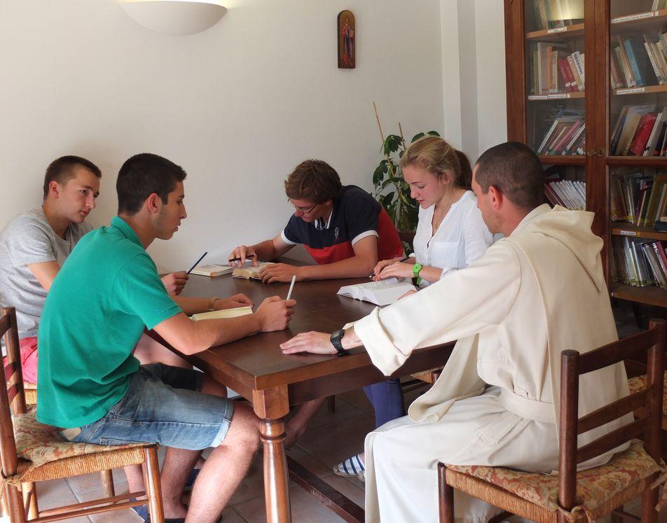Des adolescents étudient avec un moine