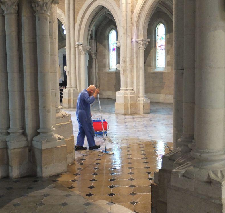 Un frère passe la serpillère sur le sol de la nef, vidé de ses bancs
