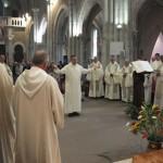 Frère Joseph chante debout les bras en croix