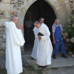 le père abbé applaudit le novice à la sortie de l'église