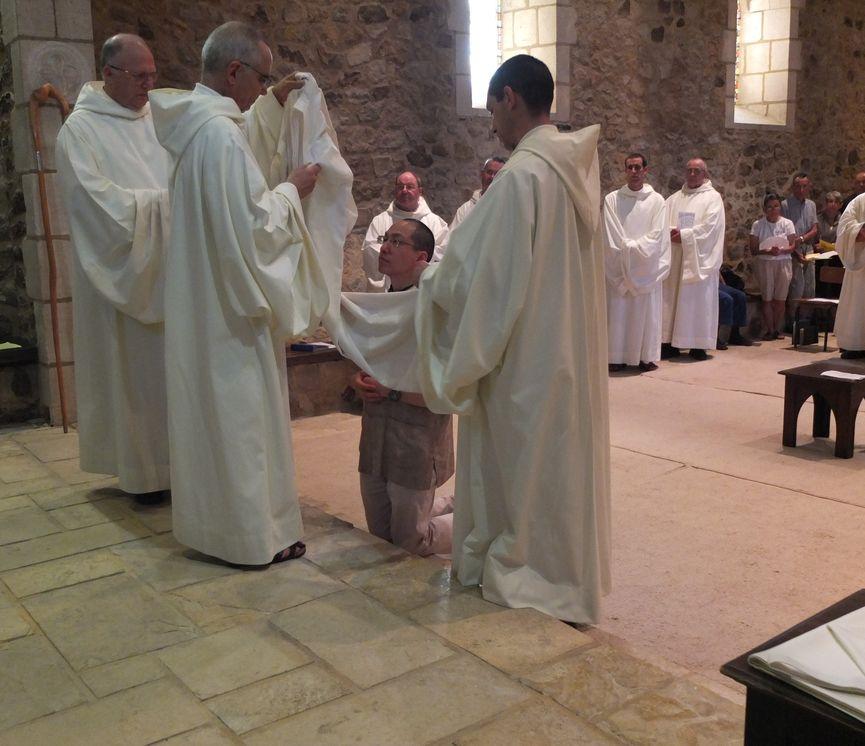 Le père abbé déplie l'habit pour le passer au postulant