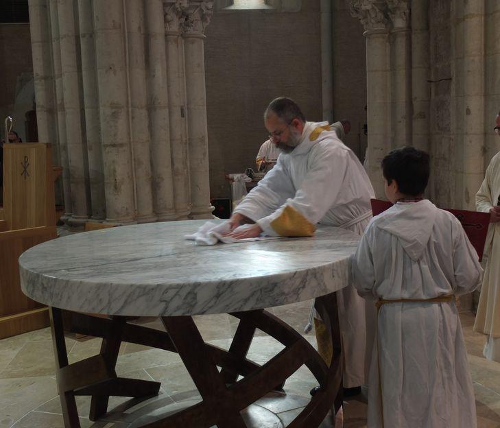 Un servant d'autel essuie le surplus de saint chrême