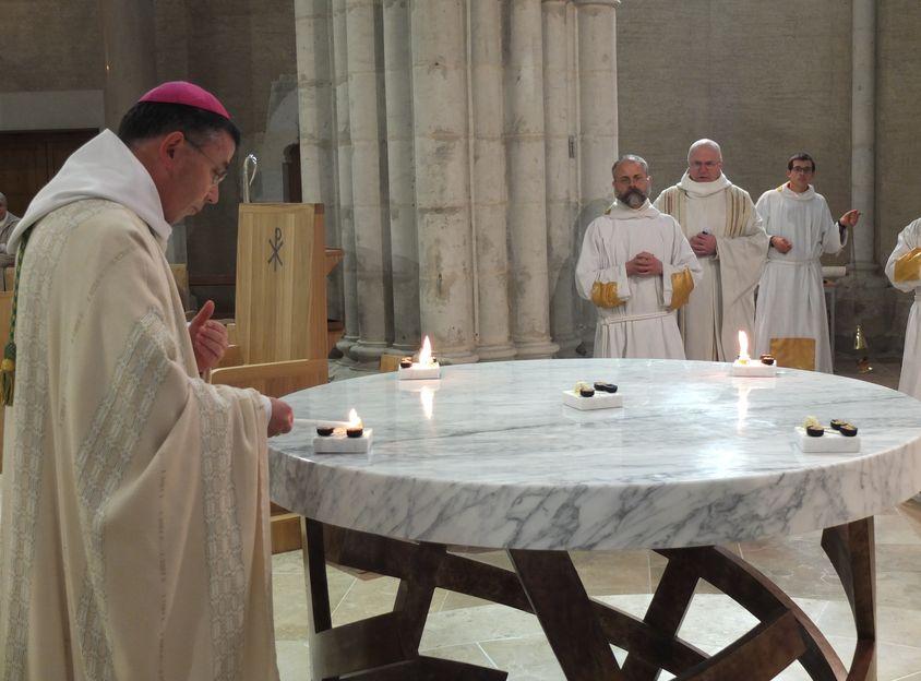 L'évêque allume les charbons qui brûleront l'encens