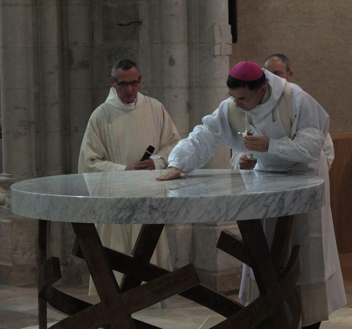 l'évêque répand le saint chrême sur l'autel