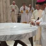 l'évêque verse le saint chrême sur l'autel