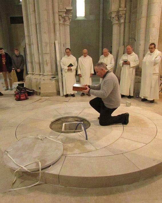 Un prêtre descend le reliquaire dans la fosse