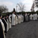Frères et soeurs en rang autour de la croix de procession attendent la sortie de l'évêque