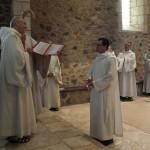Le novice, face au père abbé, reçoit un nouveau nom