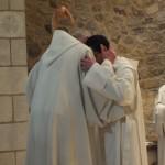 Echange d'une accolade de paix entre le père abbé et le novice