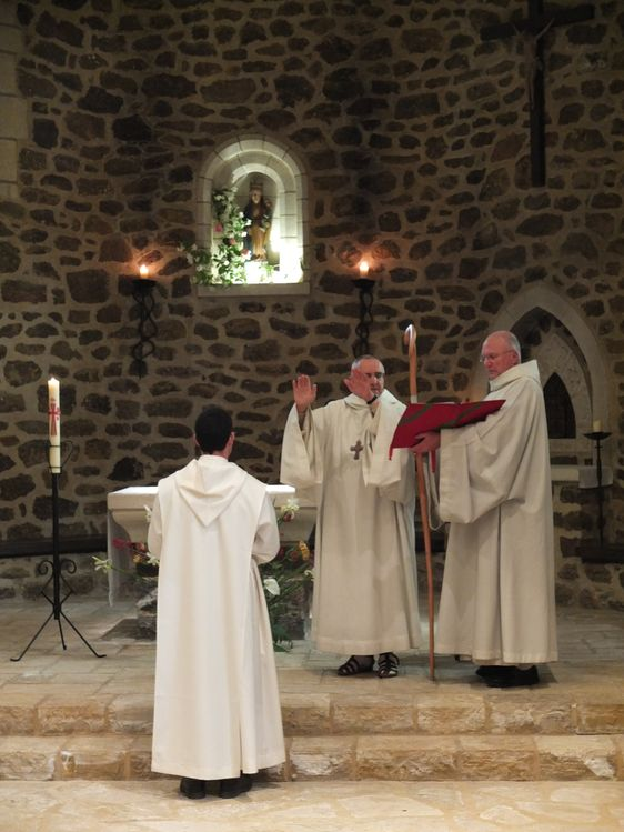 Les mains étendues, le père abbé bénit le novice