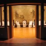 Les frères sont assis en rond dans la salle du chapitre et écoutent le père abbé.