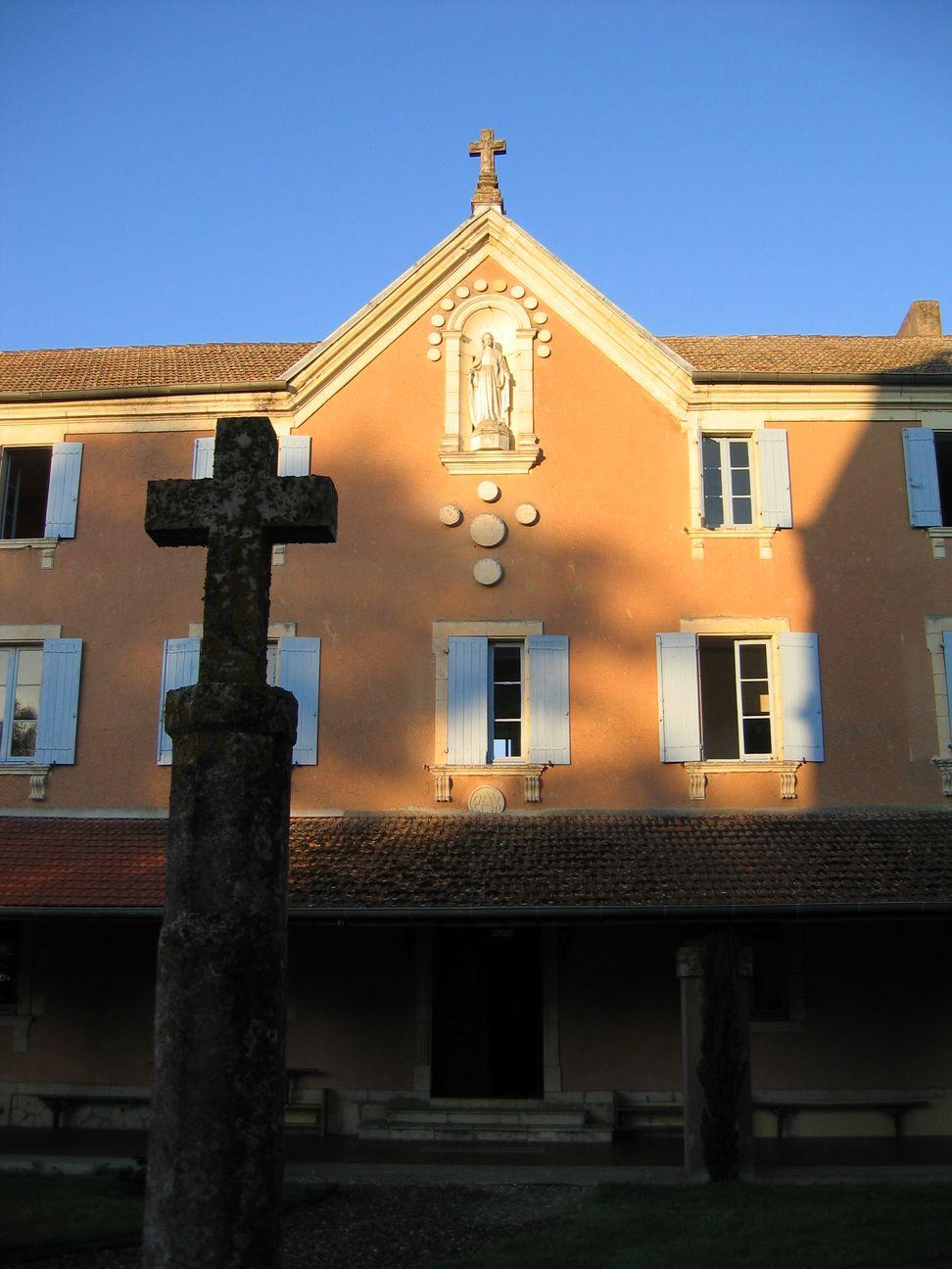Vue du cloître, la façade rose du monastère est caressée par le soleil d'un matin d'été. A son sommet, la Vierge veille sur le cloître. En premier plan une croix de pierre habillée de lichens ocres-jaunes.