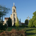 Le clocher de la Grande église s'élève vers le ciel. La Vierge, à son sommet, veille le pays de Chalosse. La vue est prise du petit jardin qui fait face à l'église.