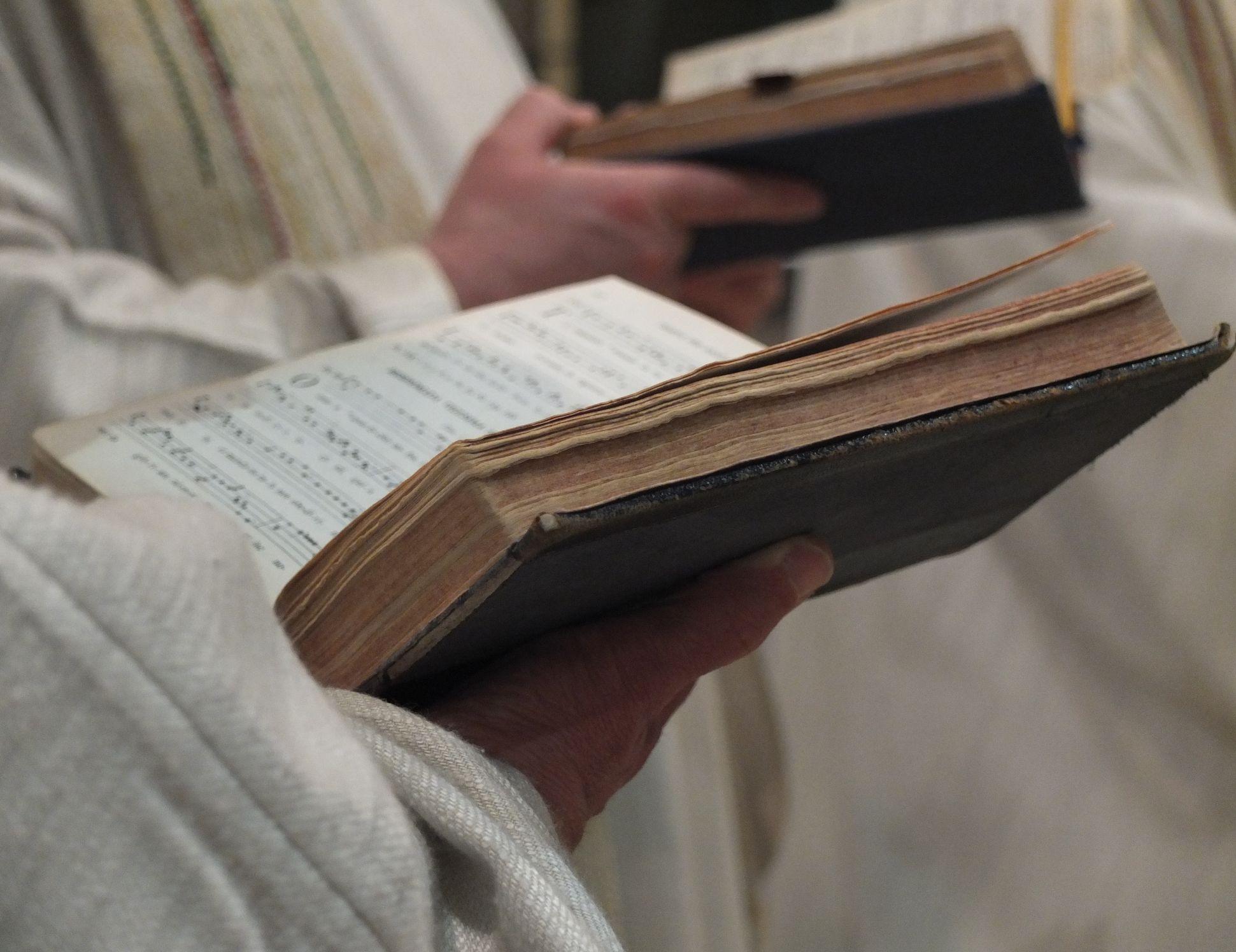 """Des livres de chant dans les mains des moines. On les appelle """"graduels"""", et ils servent pour chanter le Grégorien durant la messe."""
