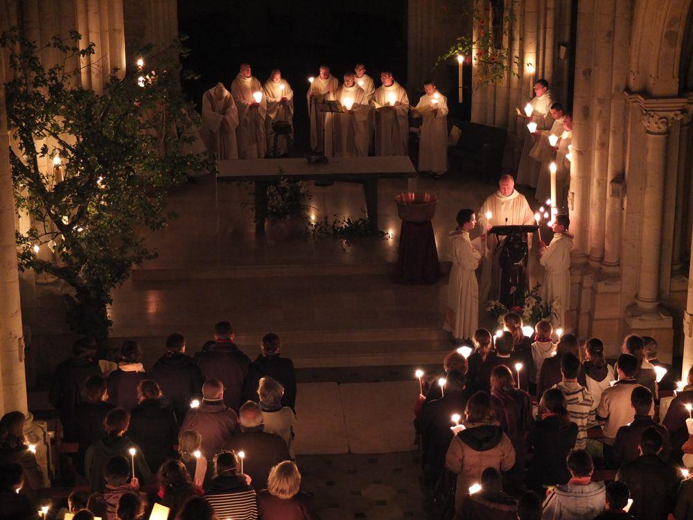 Dans la grande église, illuminée seulement par les cierges et vue depuis la tribune de l'orgue, un prêtre chante l'Exultet à l'ambon, sur la gauche. La communauté se trouve au fond, et les autres fidèles par devant. Le cierge pascal, sur la gauche se trouve dans un arbre fleuri et illuminé. Devant l'autel, la cuve baptismale est prête pour le rite de l'eau.