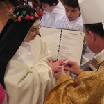 Photo en plongée sur l'évêque passant une alliance au doigt d'une sœur revêtue du voile noir et d'une couronne de roses.