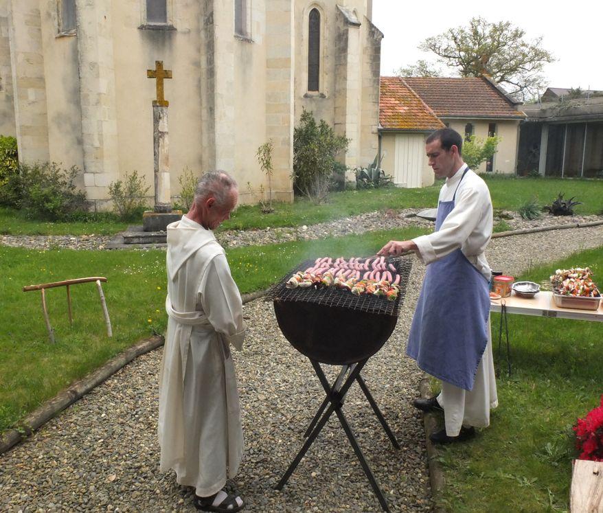Un frère fait griller des saucisses sur un barbecue tandis qu'un autre regarde attentivement.