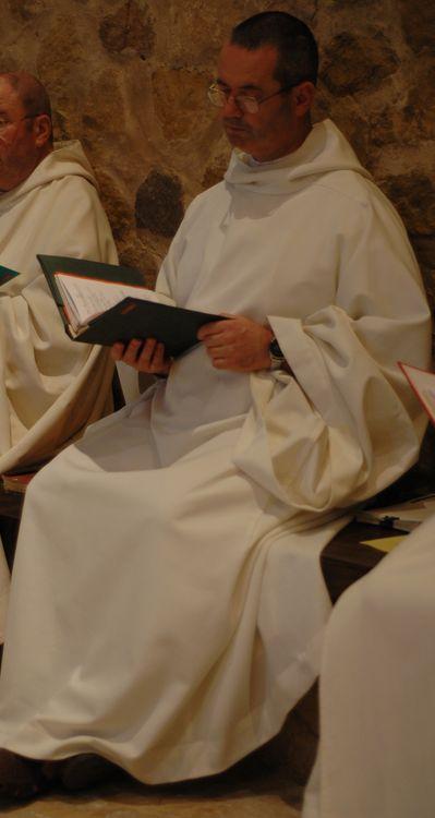 Un frère assis et tenant son livre de chant célèbre l'office avec ses frères. Derrière lui apparait le mur de pierres de la Vieille église.