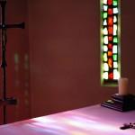 La lumière du soleil projette les couleurs du vitrail sur l'autel.