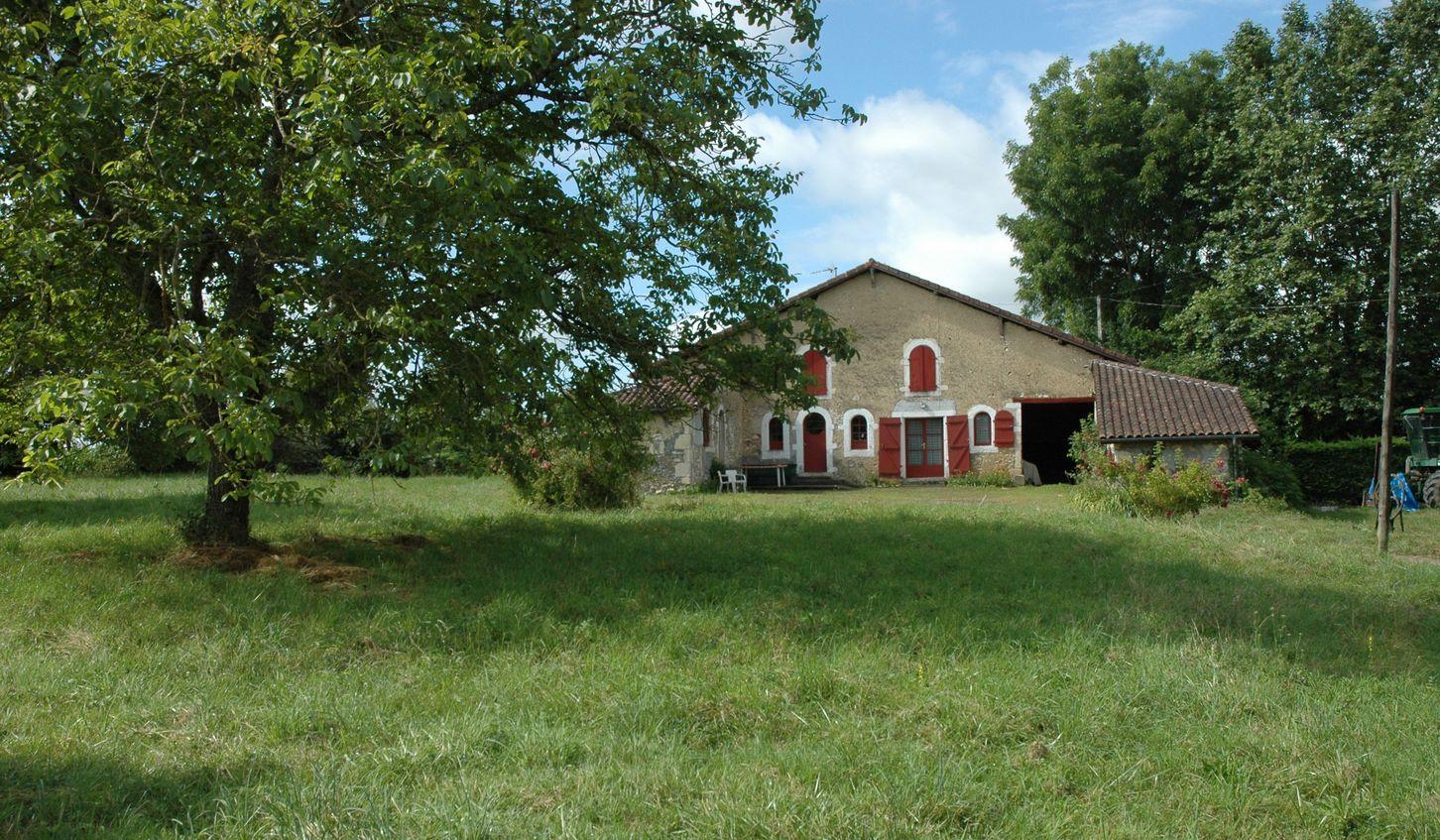 Maison landaise, basse avec un toit à longues pentes et des volets rouges.