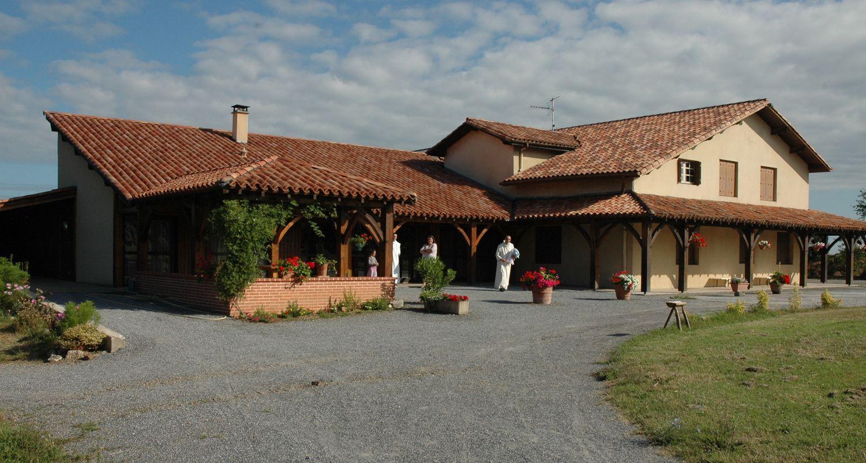 Cour du bâtiment d'hôtellerie. La galerie en bois et les fleurs lui donnent un air de maison familiale.